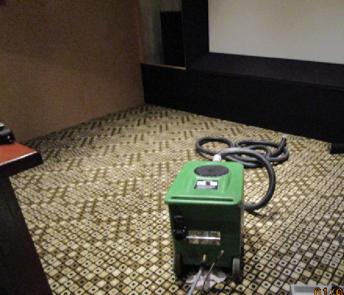 home theater room with carpet and green extraction machine in place