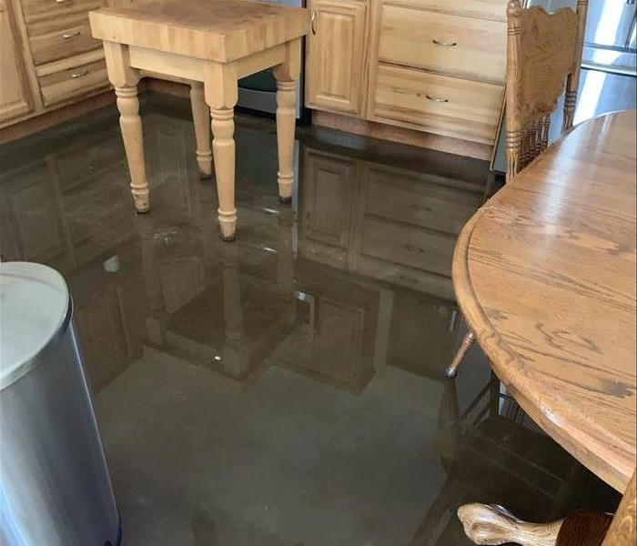 Picture of images reflecting in the water on the kitchen floor