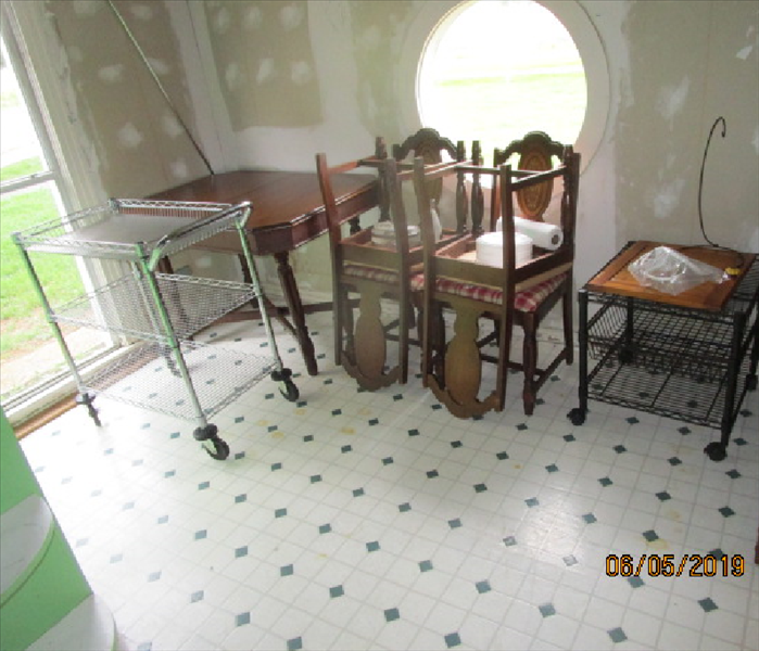Picture of the eat in area after cleaning, with the wallpaper removed and the table & chairs stacked to one side
