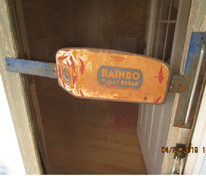 Rainbow Bread door handle sing push on an old fashion screen door.