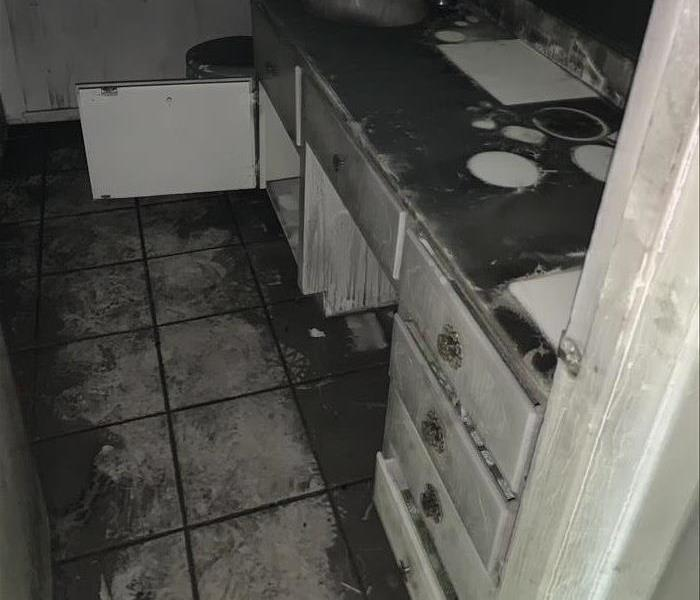 A heavily sooted vanity with clean white spots where items on the vanity had been during the fire