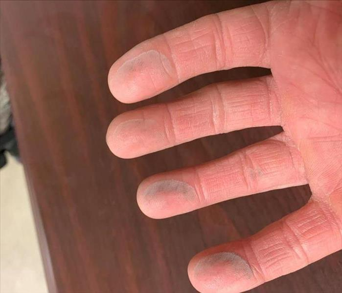 Hand with soot on fingers after being wiped across a previously cleaned desk