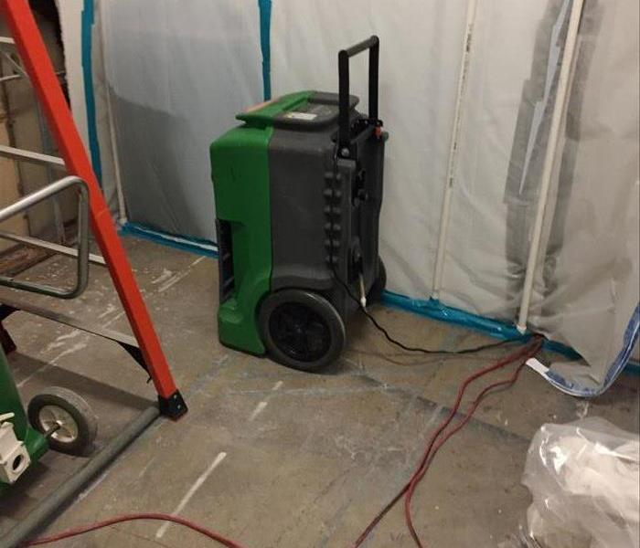 Dehumidifier inside a mold containment chamber