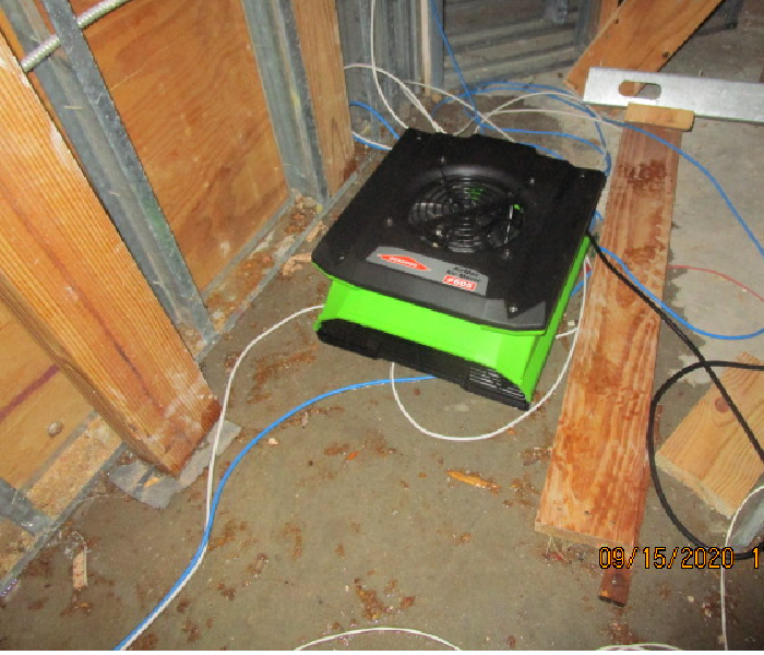 A low profile air mover/fan surrounded by water and building framing